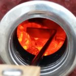 Stocking the hot charcoal with the ash cleaning tool through the smokin chip feeder port, without opening the Saffire