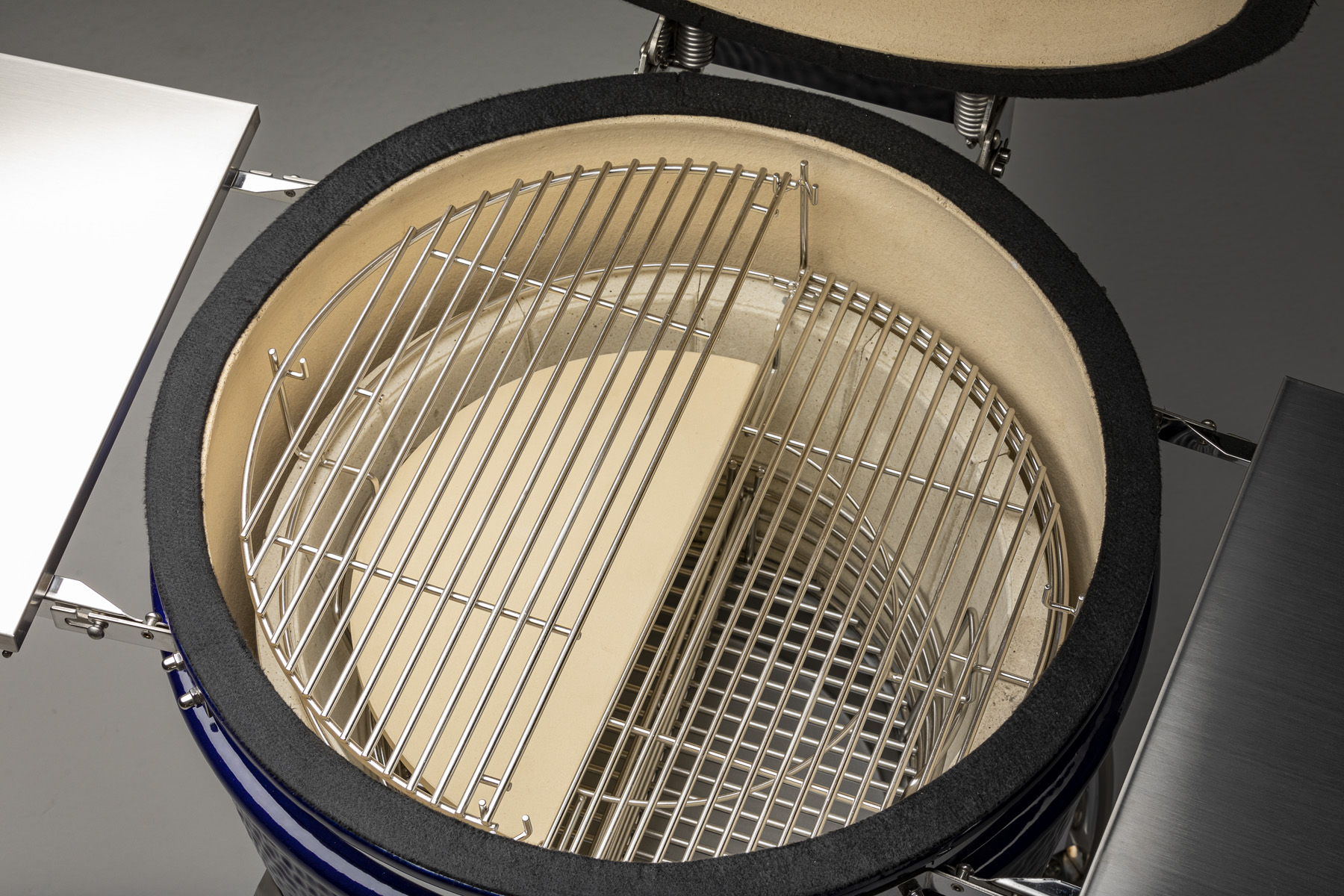 A Platinum Saffire grill is shown with the Multi-Grid, Two-Piece Ceramic Heat Deflector, Charcoal Basket and Ash Pan showing.
